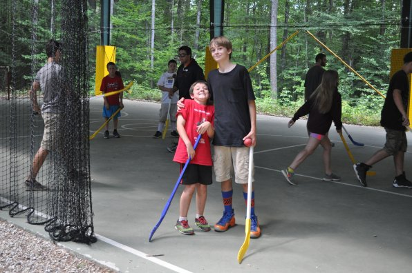 Holden Kenne and Aiden Sloan take a break from street hockey to demonstrate camp cameraderie. Or something.