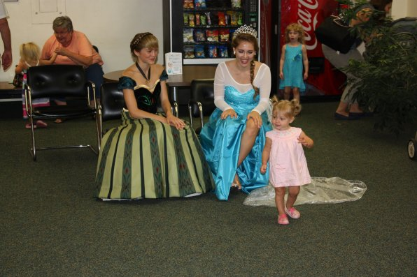 An excited but shy girl runs back to her mom after getting up close and personal with the princesses.
