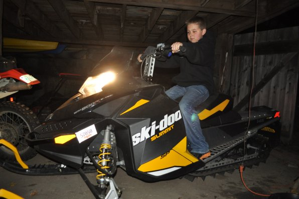 Forget the 12 days of Christmas . . . Joshua Raymond has been waiting 12 years to tun 12 on 12/12/12. Here he hops on Dad's snowmobile – an item on both his birthday and Christmas wish lists!