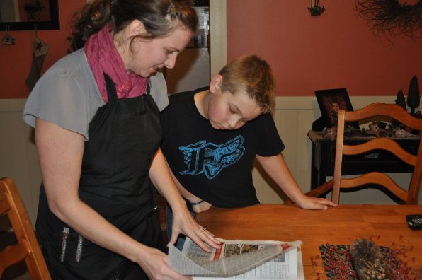 Joshua Raymond looks over some snowmobile race results with his mom, Heather Philbrook.
