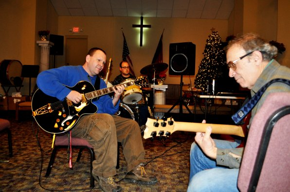Rich Doyle (left) of the Salvation Army's McKenna House jams with residents William LaBombard (center) and Harry Rosen (right) during one of the house's weekly music therapy sessions in mid-December.  As many as a dozen residents have attended the weekly gathering.