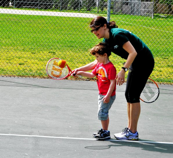 Recreation Supervisor Laura Bryant teaches Max Buckland the finer points of playing tennis with a giant orange ball during the summer of 2013.