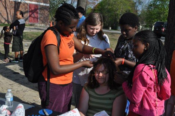Autumn Gove has her hair braided by Francine Ingabire, Kitana Matthews, Vanessa Kwizera and Hope Elonga.