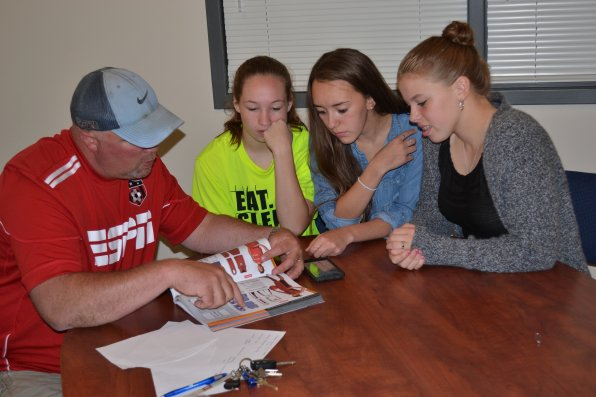 Girls coach Dave Huckins goes over the options with players Megan Johnston, Sammi Osborne and Abby Grandmaison.