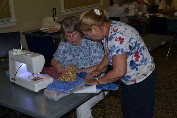 Betty Cate and Donna Severance discuss something to do with quilting.