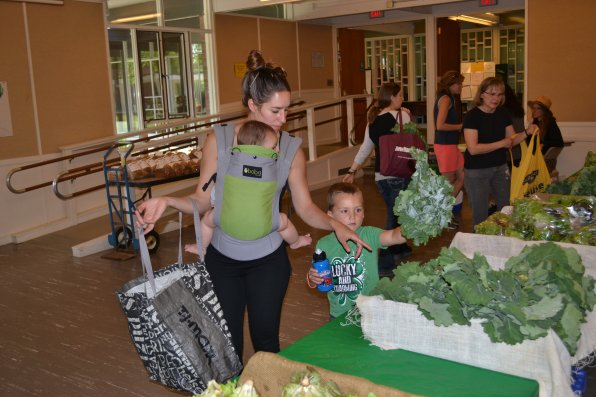 Lexxton helps his mom Justine Kelley pick out some kale, while Liviana enjoys the ride