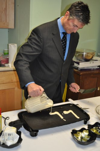 Michael Palmieri, president and CEO of Havenwood Heritage Heights, pours the beginnings of the name 'Leo' in pancake form.