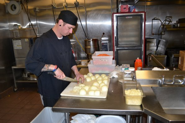 Ryan Blazon of the Concord Co-op chops what feels like a million onions for a batch of chicken noodle soup, the best seller at the Co-op's soup station.