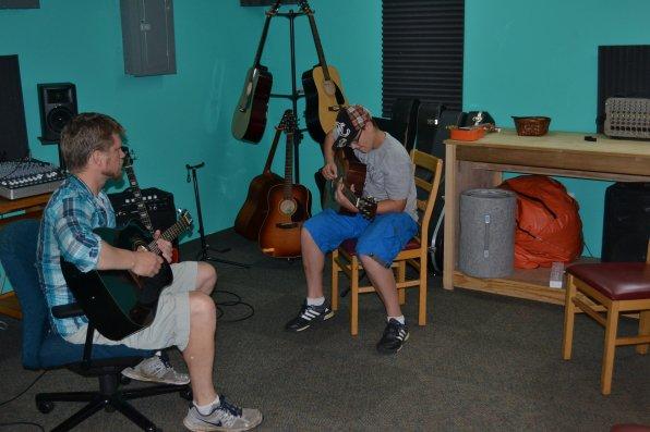 Ron Noyes listens as Josh Shaw plays a few chords from Metallica's 'Enter Sandman.'