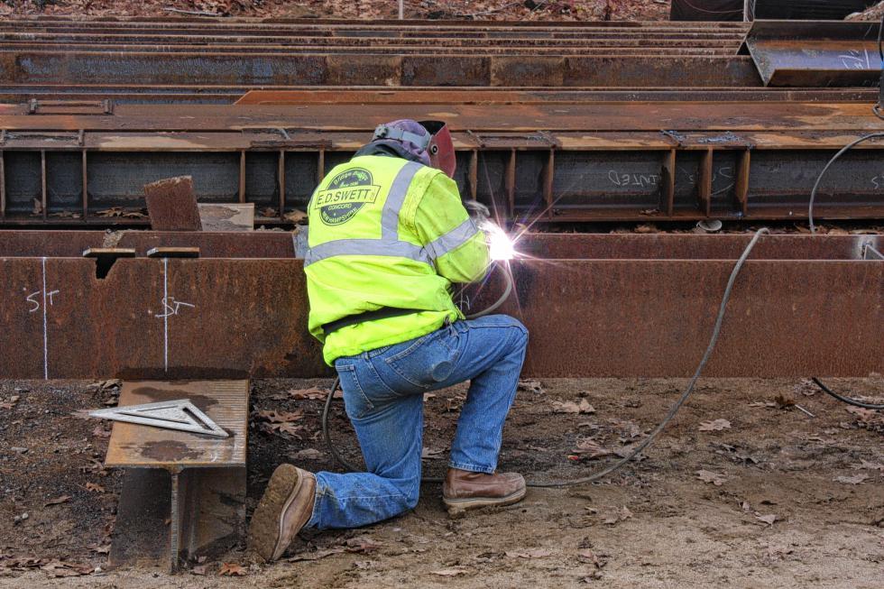 Joe Symonds with E.D. Swett welds part of a cap that will go on a trestle of the new bridge. (JON BODELL / Insider staff) -