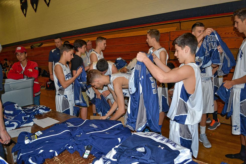 Members of the boys varsity squad look over the new away jerseys, while wearing the new home uniforms. (TIM GOODWIN / Insider staff) -