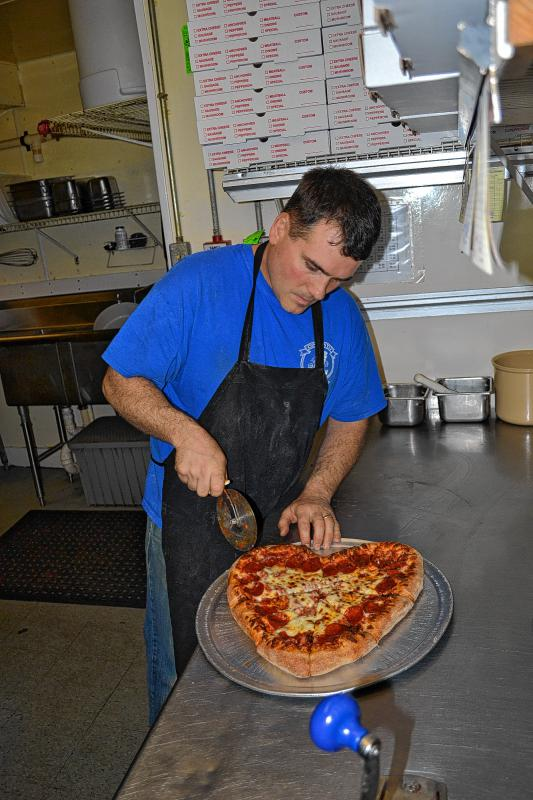 Finally, Dave Constant slices the pizza. Sometimes people will request that the pizza not be sliced, so as not to compromise the shape. Just let them know if you want it cut or not. It's delicious either way! (TIM GOODWIN / Insider staff) -