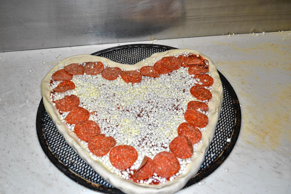 Now comes the fun part: sauce, cheese and pepperoni. Dave Constant said pepperoni is the most popular topping for the heart pizzas. (TIM GOODWIN / Insider staff) -
