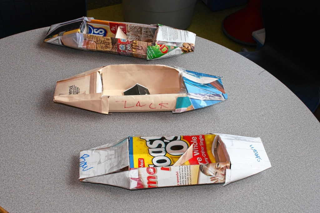 as you can see. Top right: Here's what this project is all about: teamwork. One person creases the board with some roller device while others help hold everything down. Bottom right: Fifth-grade teacher Mike Pelletier and a student do pushups on top of some panels of cardboard that had just been glued together. If you're going to apply pressure to a bond