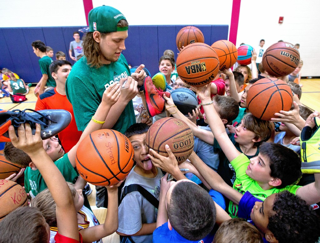 Boston Celtic PF/C Kelly Olynyk gets mobbed by kids seeking autographs on just about anything they own at Matt Bonner's basketball camp Thursday at Abbot-Downing Elementary school.