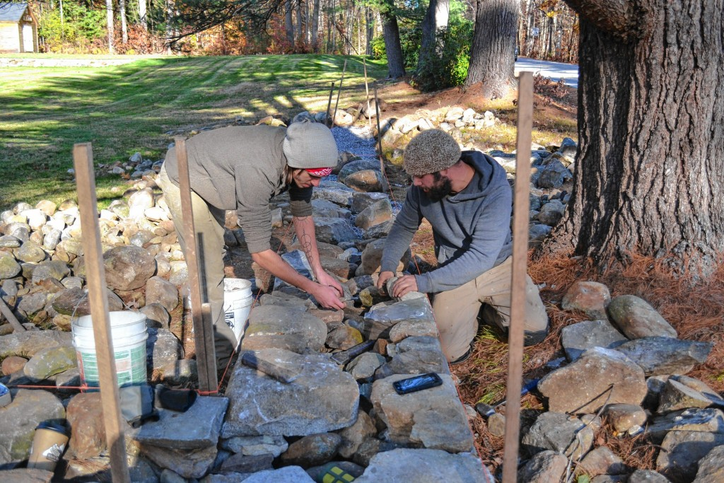 Nate Vance, left, and Matt Persechino of Contoocook Stone Works add stones to a wall they have been building on Hopkinton Road.