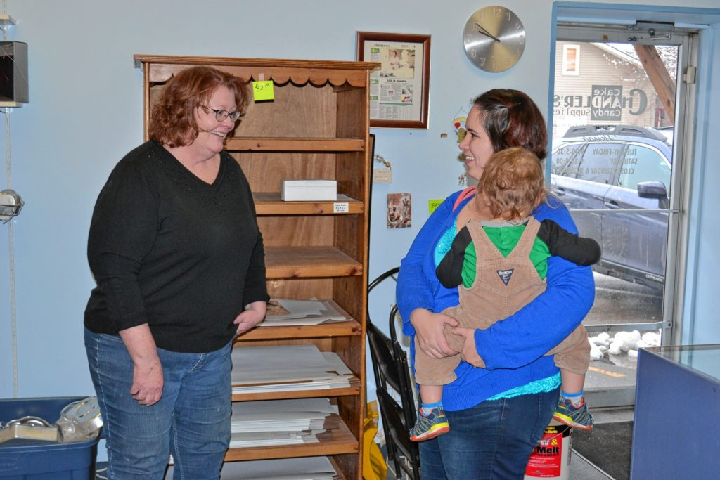 Chandler's Cake and Candy Supplies owner Sue Chandler (left) talks with longtime customer Jen Evans, who is holding her 2-year-old son Lewis.