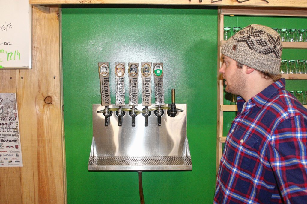 Marketing director Ryan Maiola shows off the beers on tap at Henniker Brewing Co. last week,(JON BODELL / Insider staff)