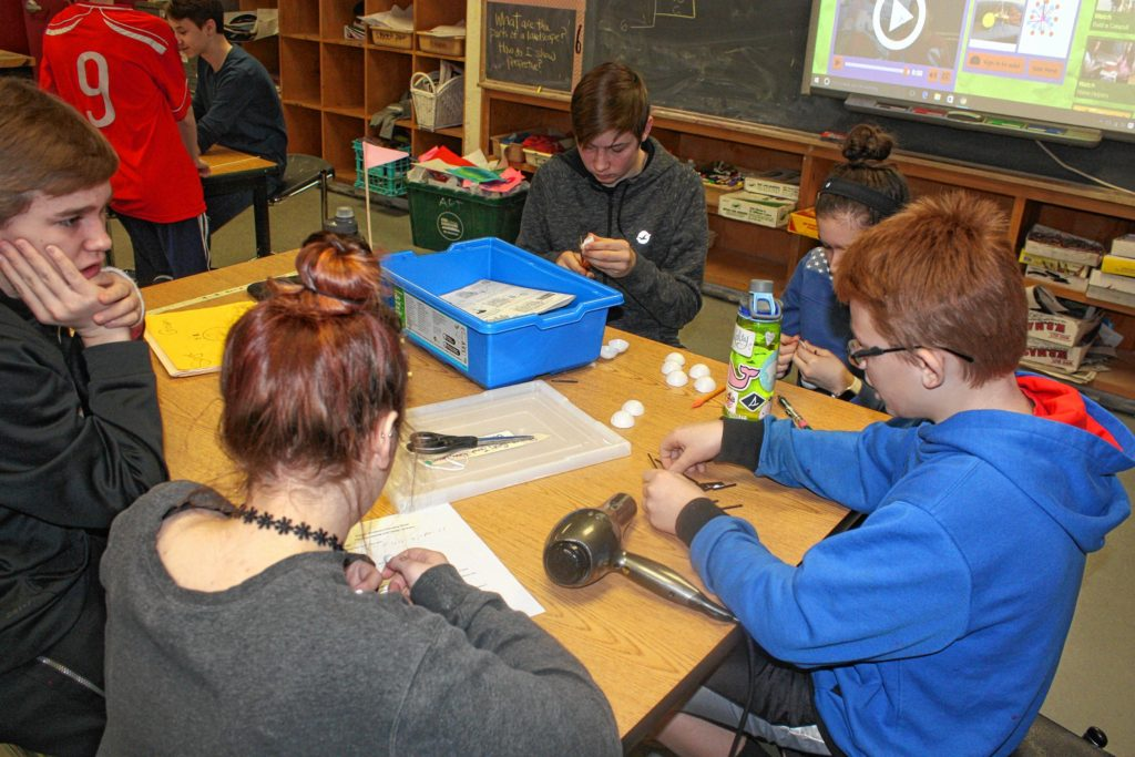From left: Students Giovanni Carone, Saige Reed, Damien McRae, Emma Fleischman and Jonah Wachter work together on their Strandbeest project at Rundlett Middle School last week. Everybody had a different job all working toward the same goal, letting each student put his or her skills to use in the best way.(JON BODELL / Insider staff)