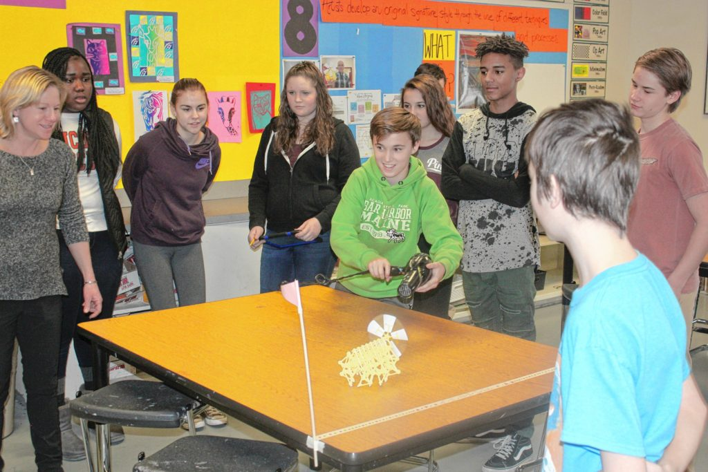 Cameron Detwiller (center) uses a hair dryer to power his Strandbeest while (from left) teacher Stephanie Bednaz, Rose Fornor, Lorelei Ford, Kathleen Shoemaker, Ava Corrente, Terrel Dixon, Nathaniel Bowers and Steven Martin look on during art class at Rundlett Middle School last week. The students spent the previous week or so building the Strandbeest, and this shot was taken during a race against another team of students.(JON BODELL / Insider staff)