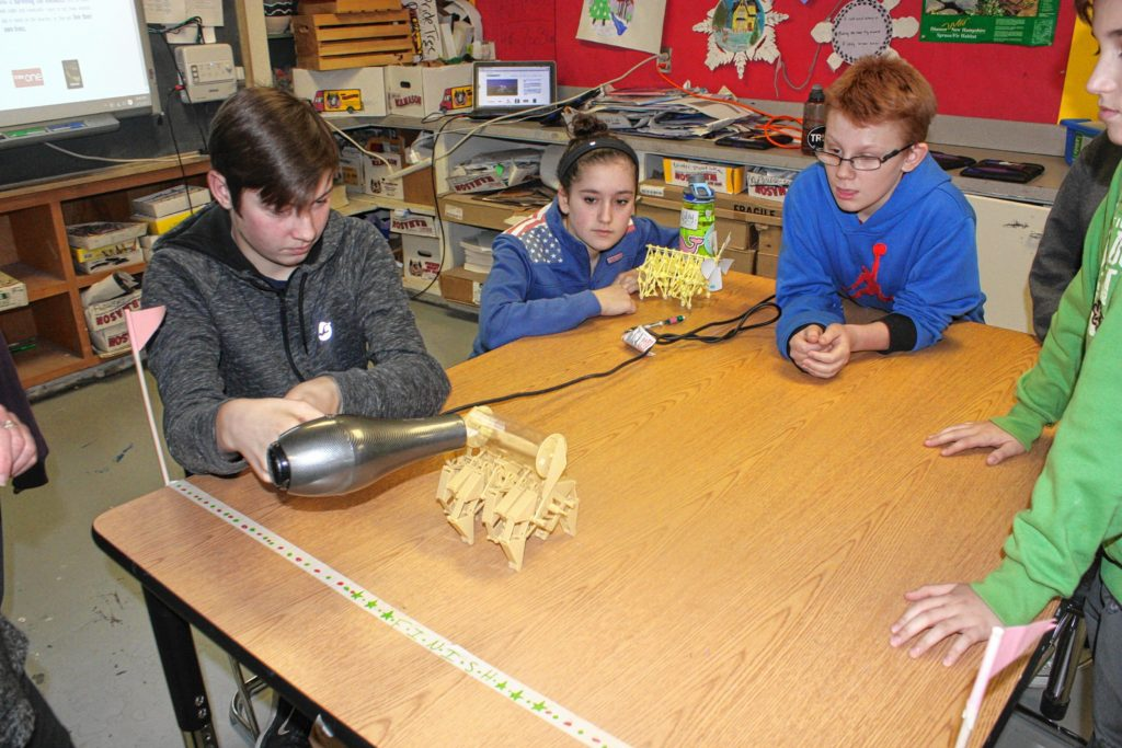 Students Jonah Wachter (left), Emma Fleischman and Damien McRae (right) check out a different Strandbeest model, this one a rhinoceros. There are two models of Strandbeest currently available for sale, and the eighth-grade art classes have all been working on the same one, called Animaris Ordis Parvus.(JON BODELL / Insider staff)