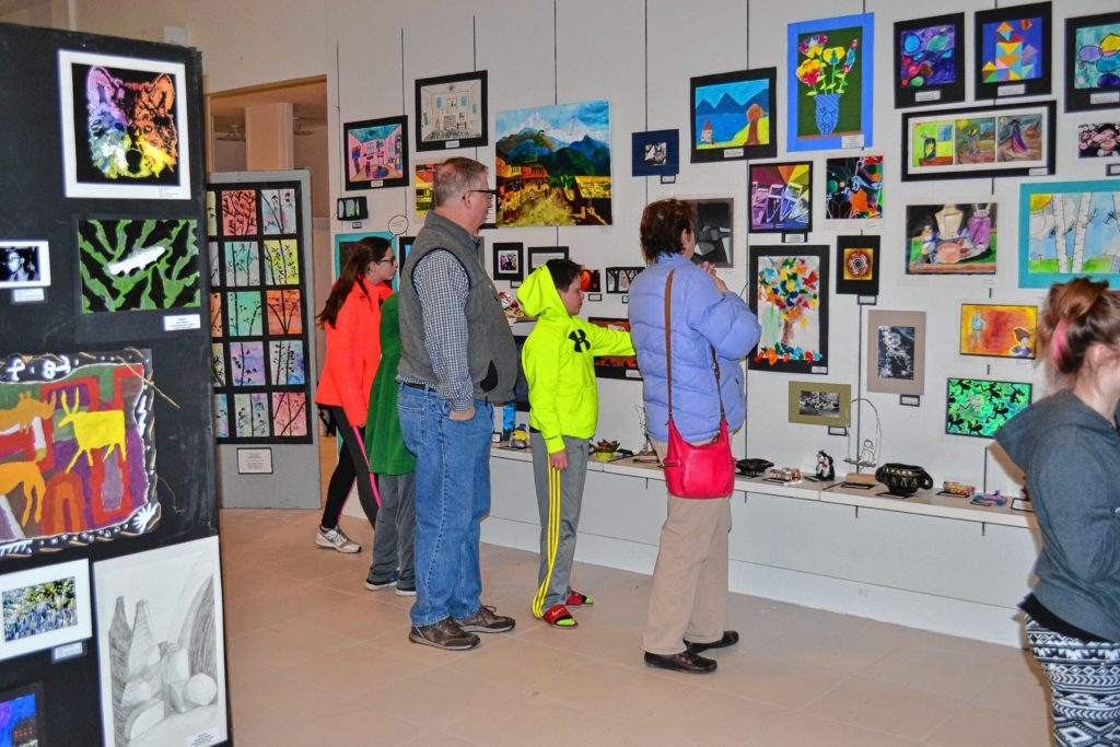 A group of art enthusiasts peruse the Youth Art Month show.