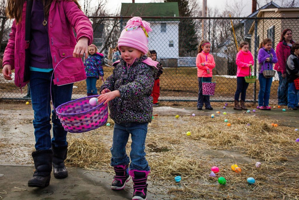 Isabella Harder, 2, of Pembroke drops a plastic egg into the basket held by her sister Madison Osborne, 9, at the start of the annual Easter egg hunt put on by the Boys & Girls Club of Suncook at Whitten Street Park in Allenstown on Saturday morning, April 4, 2015.