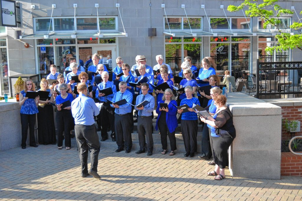 The Concord Chorale put on a flash-mob style show outside O's and Red River on Friday. Tim Goodwin