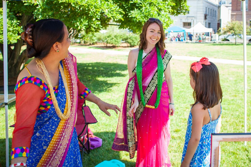 Corrin Foley (center) of Goffstown tries on a saari with the help of Nar Sharma (left) during the Concord Multicultural Festival downtown on Saturday, June 25, 2016. Sharma had a variety of garments from across South Asia for visitors to try on. (ELIZABETH FRANTZ / Monitor staff) Elizabeth Frantz