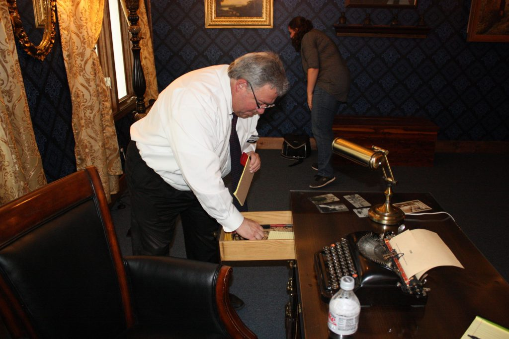 Advertising Director Tim Brady looks for clues in a desk at Escape Room Concord last week.  JON BODELL / Insider staff