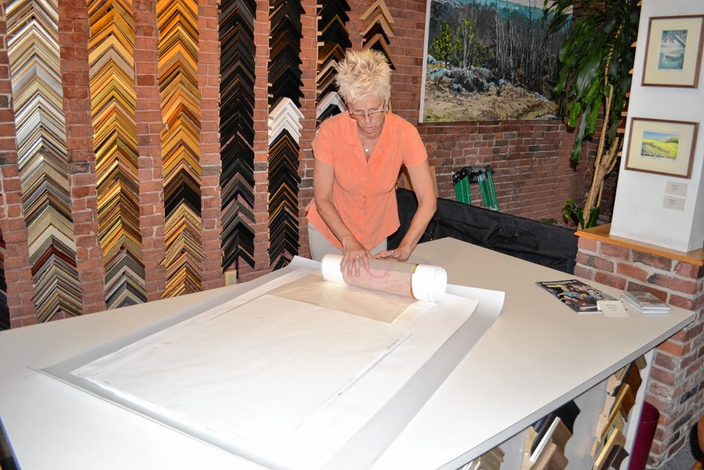 McGowan Fine Art owner Sarah Chaffee carefully rolls up work to send back to one of her many artists. With moving to a smaller location, she won't have as much room for inventory. TIM GOODWIN / Insider staff