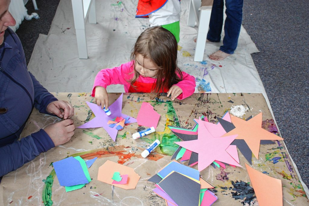 Jon's daughter, Julia, 2, applies some glue to a paper star during Paint Outside the Box art class at Rattlebox Studio last Thursday. At this art class, you never know what kinds of things the kids will make -- or how they'll make them. JON BODELL / Insider staff