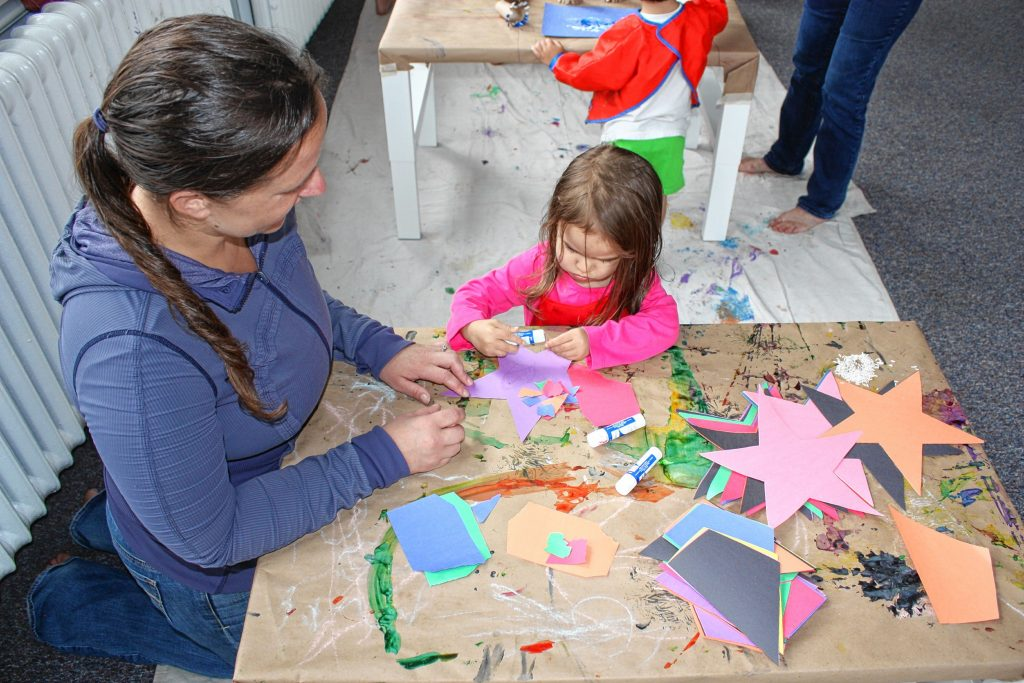 Jon's daughter, Julia, 2, puts glue on a paper star while her mom, Aimee, helps out during Paint Outside the Box art class at Rattlebox Studio last Thursday. JON BODELL / Insider staff