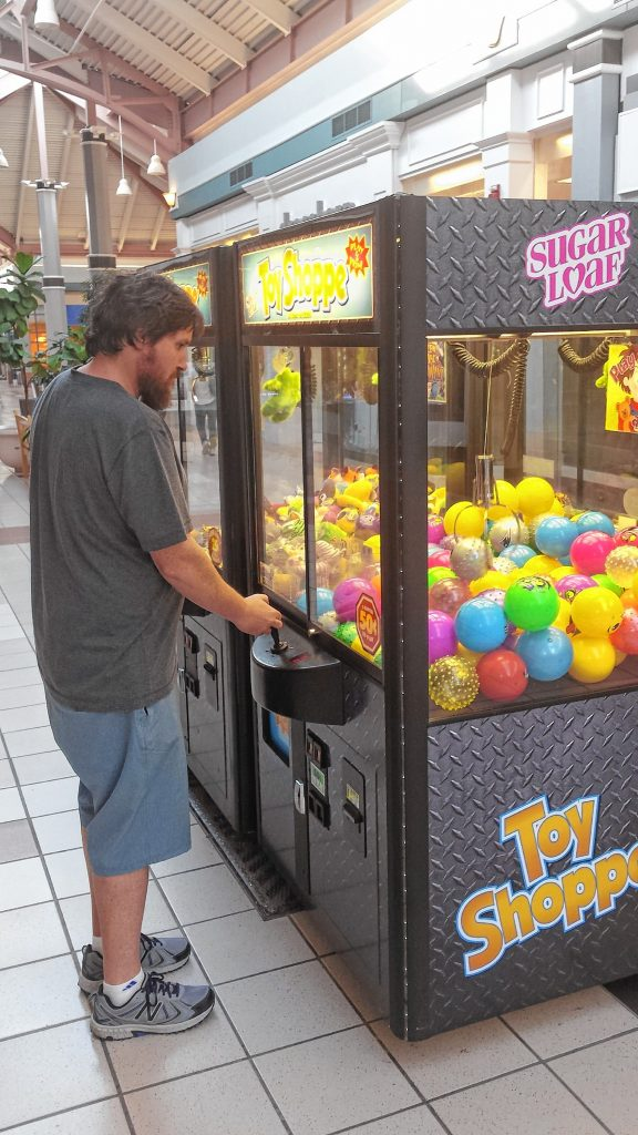 Tim lines up the claw with one of the many fabulous prizes at one of the claw machines at Steeplegate Mall last week. Despite his patience and concentration, he came up empty-clawed. JON BODELL / Insider staff