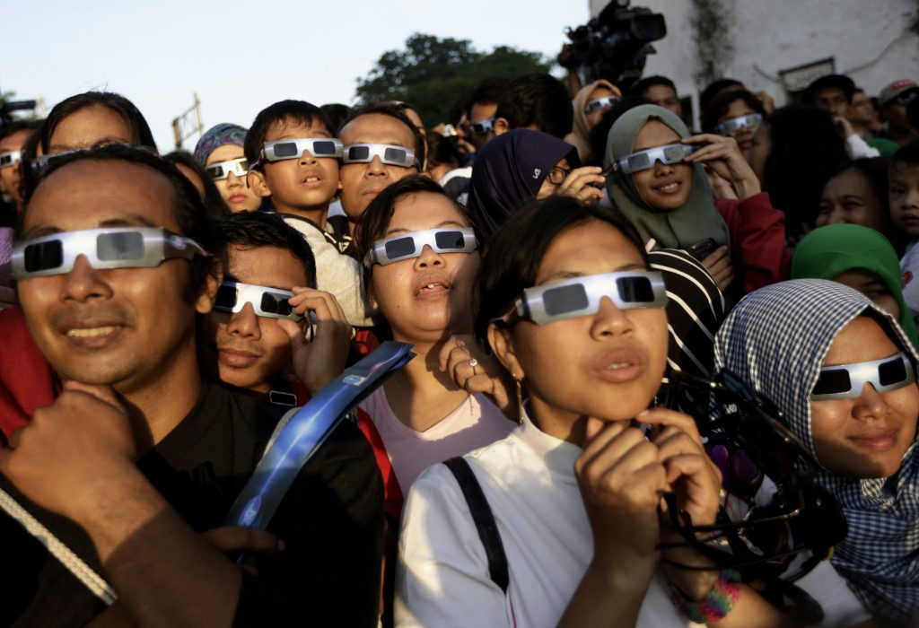 FILE - In this Wednesday, March 9, 2016 file photo, people wearing protective glasses look up at the sun to watch a solar eclipse in Jakarta, Indonesia. Doctors say not to look at the sun without eclipse glasses or other certified filters except during the two minutes or so when the moon completely blots out the sun, called totality. That's the only time it's safe to view the eclipse without protection. When totality is ending, then it's time to put them back on.  (AP Photo/Dita Alangkara) Dita Alangkara