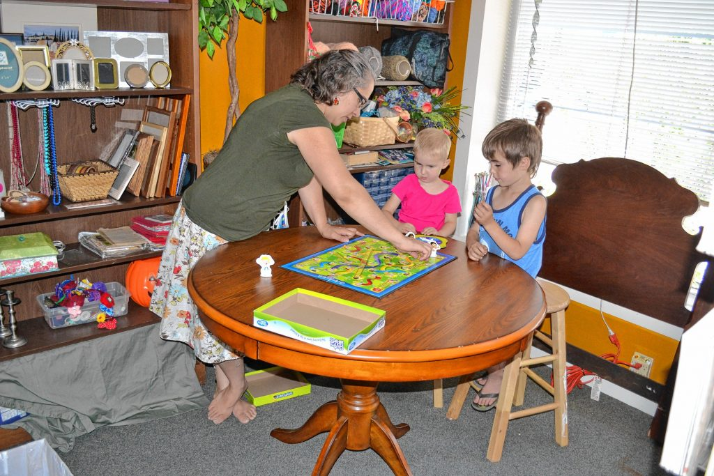WeCycle owner Katey Myers plays Chutes and Ladders with her children Kahli and Jaimisen at the North Main Street store. TIM GOODWIN / Insider staff