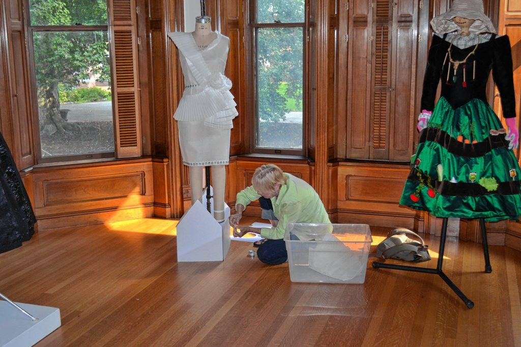 Ann Saunderson works on a dress as part of the Dressed to Draw exhibit at Kimball Jenkins last week.  TIM GOODWIN / Insider staff
