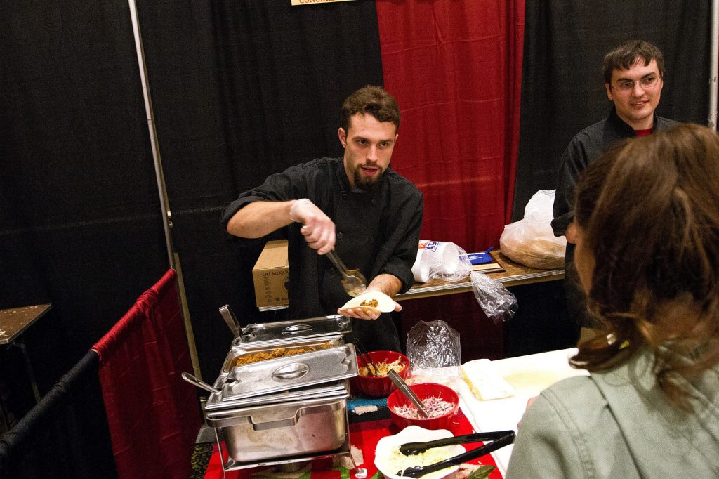 Paige Averill, kitchen manager at Hermanos, serves up mini pork burritos with Scott Jordan, cook at Hermanos, during the ninth annual Taste of Concord at the Grappone Conference Center on Thursday, Oct. 9, 2014.  (JULIE BYRD-JENKINS / Monitor staff) JULIE BYRD-JENKINS