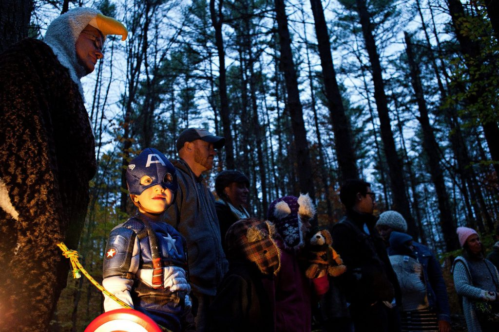 Dressed as Captain America, Indi Santana, 5, of New Market, listens to a skit by volunteers Beth McGuinn, of Canterbury, and Karen Shields, of Concord, during the New Hampshire Audubon's Enchanted Forest on Saturday evening, October 26, 2013. The Enchanted Forest returned on Saturday after a hiatus since 2004 and offers an educational alternative to haunted houses and haunted forests. The forest had several stops where skits were performed by volunteers and Audubon staff and the trail was lit by jack-o-lanterns.  (JOHN TULLY / Monitor Staff) John Tully