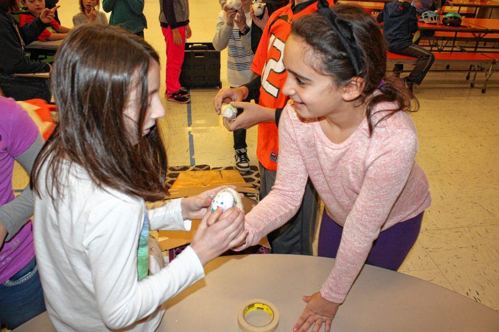 Reilly Kilngerman (left) and Sabine Karanouh inspect an egg after sending it down a ramp at Bow Elementary School last week. JON BODELL / Insider staff