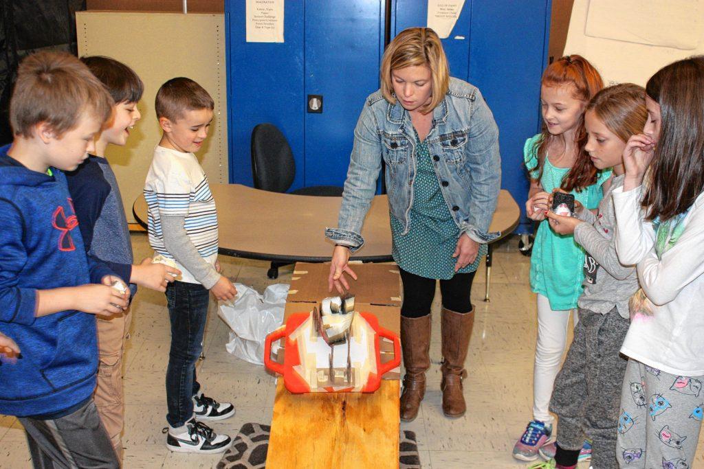Bow Elementary School health teacher Jill Pelletier helps students from Ms. Gage's fourth-grade class test their egg helmets at the school last week. JON BODELL / Insider staff