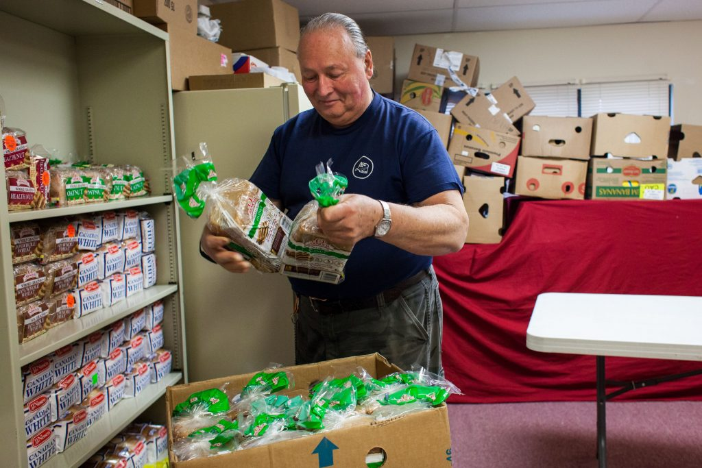 "Lenny Virgin stocks the bread shelf with donations at the Gospel Light Food Pantry on Hall Street in Concord on Feb. 15, 2017. The pantry assisted a record 43 clients on the last Saturday of January. ""The need is growing,"" Betsey said. (ELIZABETH FRANTZ / Monitor staff) Elizabeth Frantz"