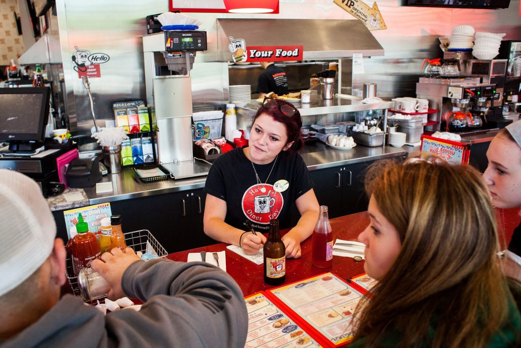 Jasmine Reinert, 18 of Salem serves customers seated at the bar at the Red Arrow Diner on Loudon Road in Concord on Tuesday, July 25, 2017. Reinert previously worked at the Londonderry location before transferring to the new Concord restaurant. (ELIZABETH FRANTZ / Monitor staff) ELIZABETH FRANTZ