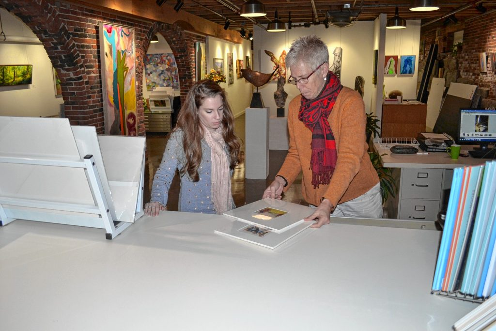 McGowan owner Sarah Chaffee (right) and Julie Hamel, the gallery's communication go-to person, look over some work in the new space at 2 Phenix Ave. TIM GOODWIN / Insider staff