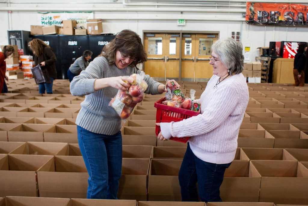 Volunteers Lisa Philbrick (left) and Patty Smith add apples to rows and rows of boxes as part of the Capital Region Food Program's Holiday Food Basket Project at the New Hampshire Army National Guard Armory in Concord on Wednesday, Dec. 20, 2017. (ELIZABETH FRANTZ / Monitor staff) Elizabeth Frantz