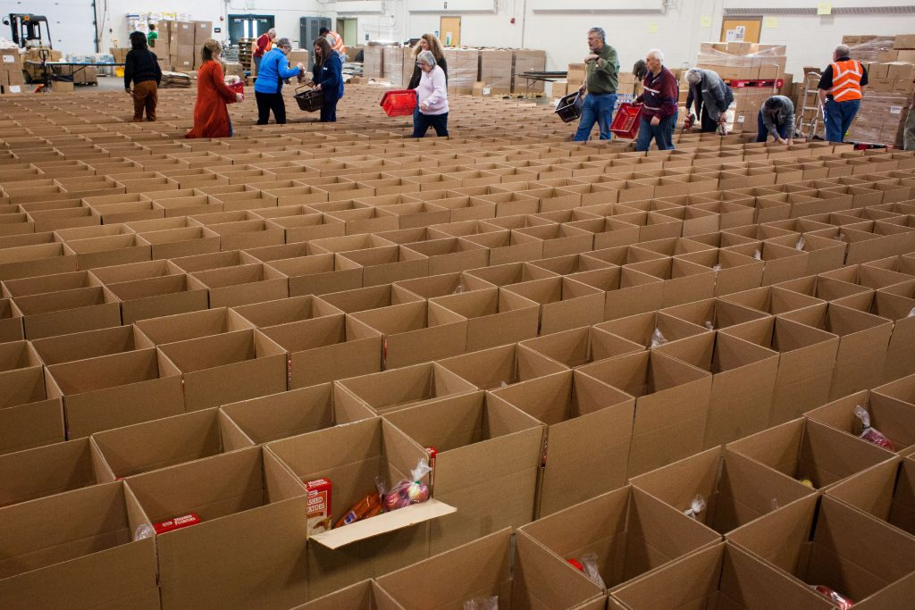 Volunteers add food to a boxes as part of the Capital Region Food Program's Holiday Food Basket Project at the New Hampshire Army National Guard Armory in Concord on Wednesday, Dec. 20, 2017. The boxes will contain enough food to last a few weeks in addition to a special holiday meal. (ELIZABETH FRANTZ / Monitor staff) Elizabeth Frantz