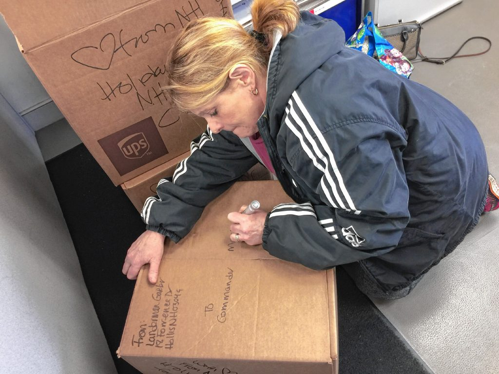 Laura Landerman-Garber fills out one of seven boxes filled with holiday cards for members aboard the USS Theodore Roosevelt. Courtesy of Laura Landerman-Garber