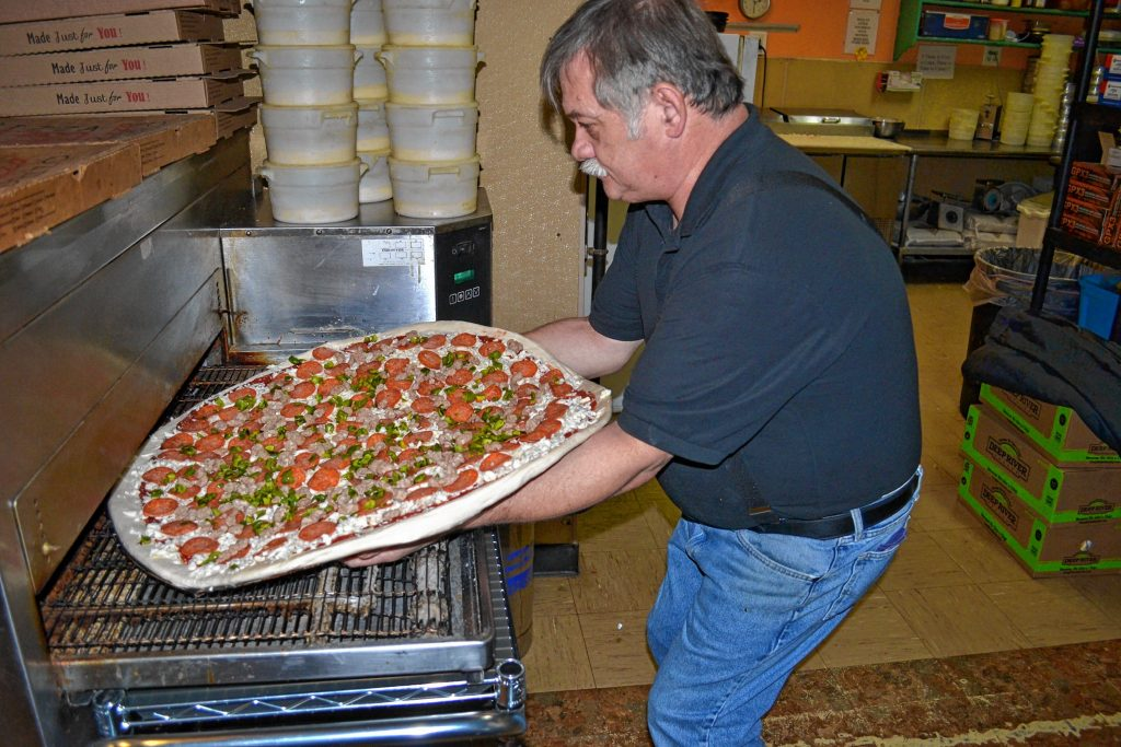 Donatello's owner Bob Boisvert puts a super dominator, loaded with pepperoni, sausage and green pepper, in the oven. TIM GOODWIN / Insider staff
