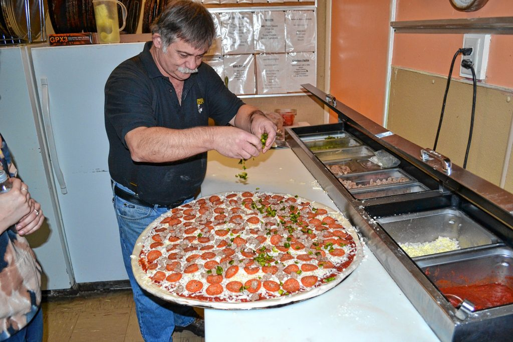 Donatello's owner Bob Boisvert adds green peppers to a super dominator. TIM GOODWIN / Insider staff