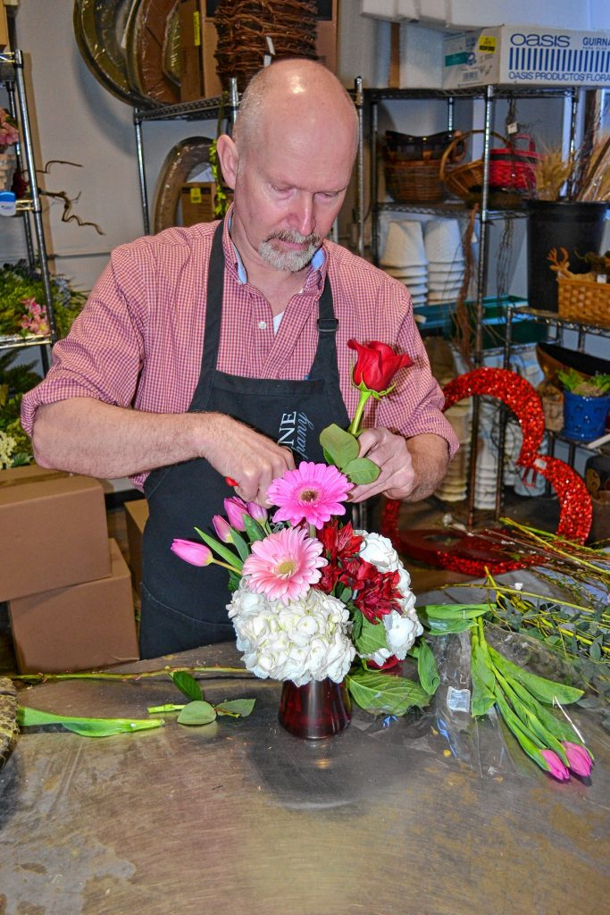 Brad Towne, owner of Cobblestone Design, puts together an arrangement of fresh flowers in preparation for Valentine's Day. TIM GOODWIN / Insider staff